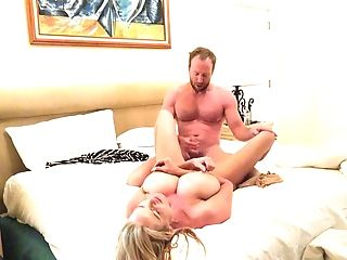 Kelly Madison takes off her dress for a rumble in a bed with a man